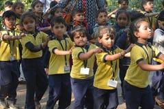 Niños de la escuela que hacen cola para arriba para recolectar Fotografía de archivo