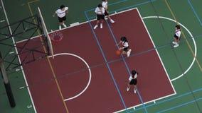 Niños de la escuela que juegan a baloncesto en una cancha de básquet metrajes
