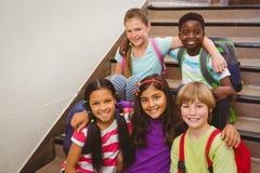 Niños de la escuela que se sientan en las escaleras en escuela Imagen de archivo libre de regalías