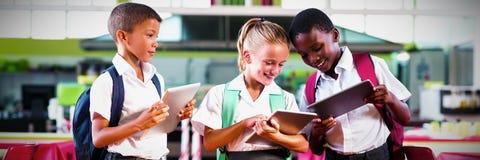 Niños de la escuela usando la tableta digital en cafetería de la escuela imagen de archivo