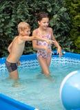 Niños de la felicidad en la piscina Fotos de archivo