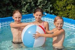 Niños de la felicidad en la piscina Imágenes de archivo libres de regalías