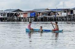 Niños de la tribu de Bajau que se divierten remando el bote pequeño cerca de sus casas del pueblo en el mar, Sabah Semporna, Mala imagen de archivo libre de regalías