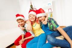 Niños de las adolescencias en la fiesta de Navidad en los sombreros de Papá Noel Fotos de archivo libres de regalías