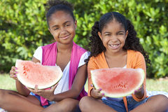 Niños de las muchachas del afroamericano que comen el melón de agua fotos de archivo libres de regalías