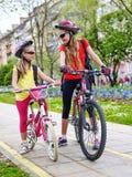 Niños de las muchachas que completan un ciclo en carril amarillo de la bici Fotografía de archivo libre de regalías