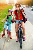Niños de las muchachas que completan un ciclo en carril amarillo de la bici Hay coches en el camino Fotos de archivo libres de regalías