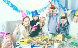Niños de los jaraneros que tienen un buen rato en una fiesta de cumpleaños Foto de archivo