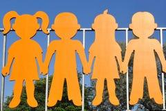 Niños de madera coloreados, objeto del arte en el parque imagen de archivo
