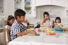 Niños de organización de la madre ocupada en el desayuno en cocina Foto de archivo