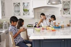 Niños de organización de la madre ocupada en el desayuno en cocina Imagenes de archivo