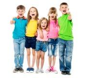 Niños de risa divertidos que se abrazan con los pulgares para arriba Fotografía de archivo libre de regalías