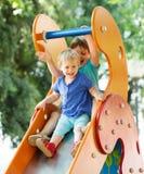 Niños de risa en diapositiva Imagenes de archivo