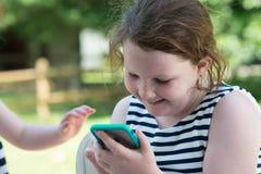 Niños de risa felices que juegan con Smartphone afuera Imagenes de archivo