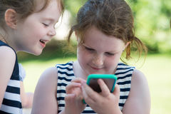 Niños de risa felices que juegan con Smartphone afuera Fotografía de archivo