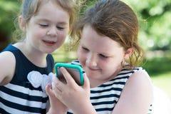 Niños de risa felices que juegan con Smartphone afuera Imagen de archivo libre de regalías