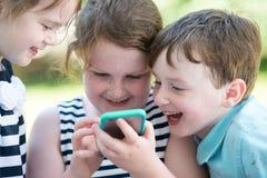 Niños de risa felices que juegan con Smartphone afuera Foto de archivo