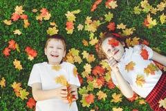 Niños de risa que mienten en la hierba que lanza las hojas de otoño en t Imagen de archivo libre de regalías