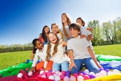 Niños de risa que se sientan en el centro del paracaídas Imagen de archivo