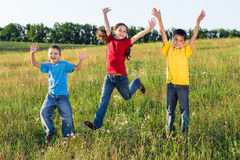 Niños de salto en campo verde Imágenes de archivo libres de regalías