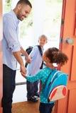 Niños de Saying Goodbye To del padre como se van para la escuela Imagen de archivo