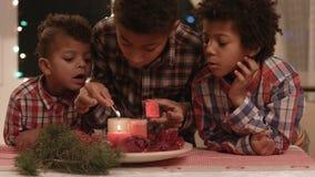 Niños del Afro que encienden velas de la Navidad metrajes