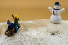Niños del concepto del invierno que resbalan abajo de la montaña nevosa Fotografía de archivo