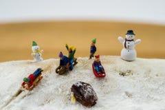 Niños del concepto del invierno que resbalan abajo de la montaña nevosa Foto de archivo