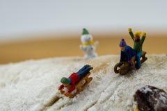 Niños del concepto del invierno que resbalan abajo de la montaña nevosa Imágenes de archivo libres de regalías