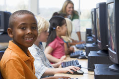 Niños del jardín de la infancia que aprenden utilizar los ordenadores Fotos de archivo