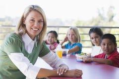 Niños del jardín de la infancia que comen el almuerzo imagenes de archivo