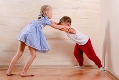 Niños del muchacho y de la muchacha que juegan en casa Fotografía de archivo libre de regalías