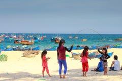 Niños del pueblo pesquero que juegan la comba en la costa arenosa imágenes de archivo libres de regalías