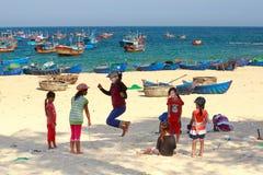Niños del pueblo pesquero que juegan la comba en la costa arenosa imagen de archivo