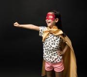 Niños del super héroe en un fondo negro Imagen de archivo