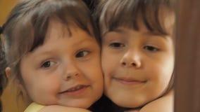 Niños delante del espejo Las hermanas están abrazando Polvo en el espejo Niñas delante de un espejo almacen de video