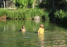 Niños desagradables en la impregnación de la ropa mojada en agua fotografía de archivo libre de regalías