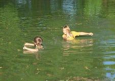 Niños desagradables en la impregnación de la ropa mojada en agua imagenes de archivo