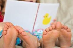 Niños descalzos que leen una historia Foto de archivo