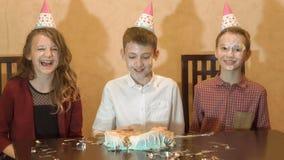 Niños despreocupados en una fiesta de cumpleaños cara del kid& x27; s en la torta y la sonrisa Fotografía de archivo libre de regalías