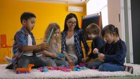 Niños diversos que juegan con construir bloques del juguete almacen de video