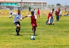 Niños diversos que juegan a fútbol del fútbol en la escuela Imagenes de archivo