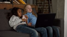 Niños diversos que miran a la show televisivo en el ordenador portátil almacen de metraje de vídeo