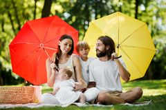 Niños divertidos con la mamá y el papá que se sientan en la manta debajo de los paraguas rojos y amarillos grandes que los cubren fotos de archivo libres de regalías