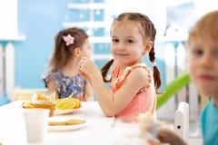 Niños divertidos del árbol que comen las frutas en centro de cuidado de día imagenes de archivo