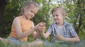 Niños divertidos del retrato dos que se sientan en la hierba en jugar del parque El muchacho que juega con un insecto, muchacha q almacen de video