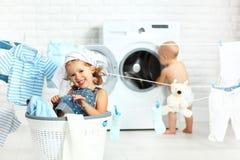 Niños divertidos hermana y hermano felices de los pequeños ayudantes en lavadero a Imagen de archivo