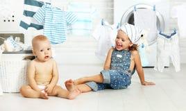 Niños divertidos hermana y hermano felices de los pequeños ayudantes en lavadero a Imagen de archivo libre de regalías
