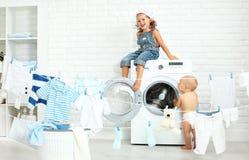 Niños divertidos hermana y hermano felices de los pequeños ayudantes en lavadero a Imágenes de archivo libres de regalías