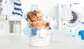 Niños divertidos hermana y hermano felices de los pequeños ayudantes en lavadero a Fotografía de archivo libre de regalías